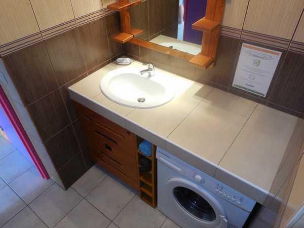 Salle d'eau avec placard et lave-linge individuel.