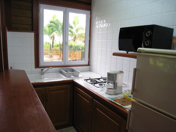 The kitchen of your cottage with a windows in front of the garden